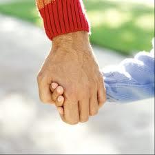 Young hand and old hand. A man walks with his grandson on the street, but we can see just their hands on a picture.